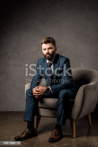 1081599130 istock photo handsome bearded businessman sitting in armchair 1081599120