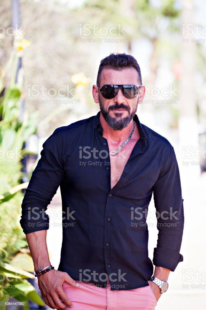 Yakışıklı sakallı moda model adam açık havada poz güneş gözlüğü ile stok fotoğrafı
