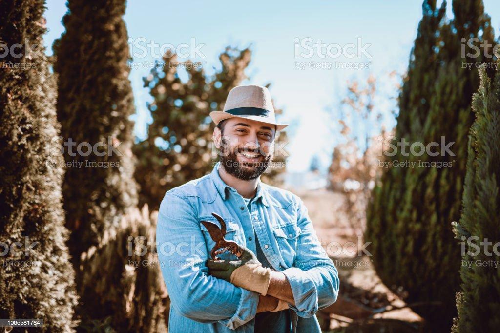 Handsome Bearded Gardener Posing In His Beautiful Garden stock photo