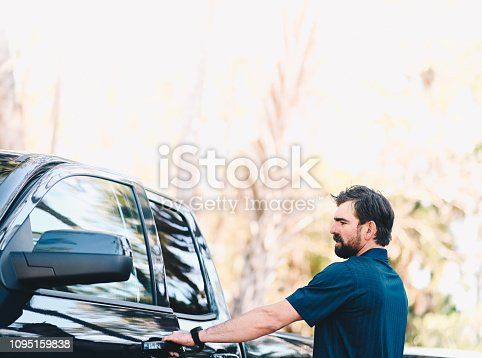 A good looking man in his 30's opens the door of a a vehicle. He wears casual clothing and seems about to head out: Looks to be spring or summer season. He is cheerful, image is candid.