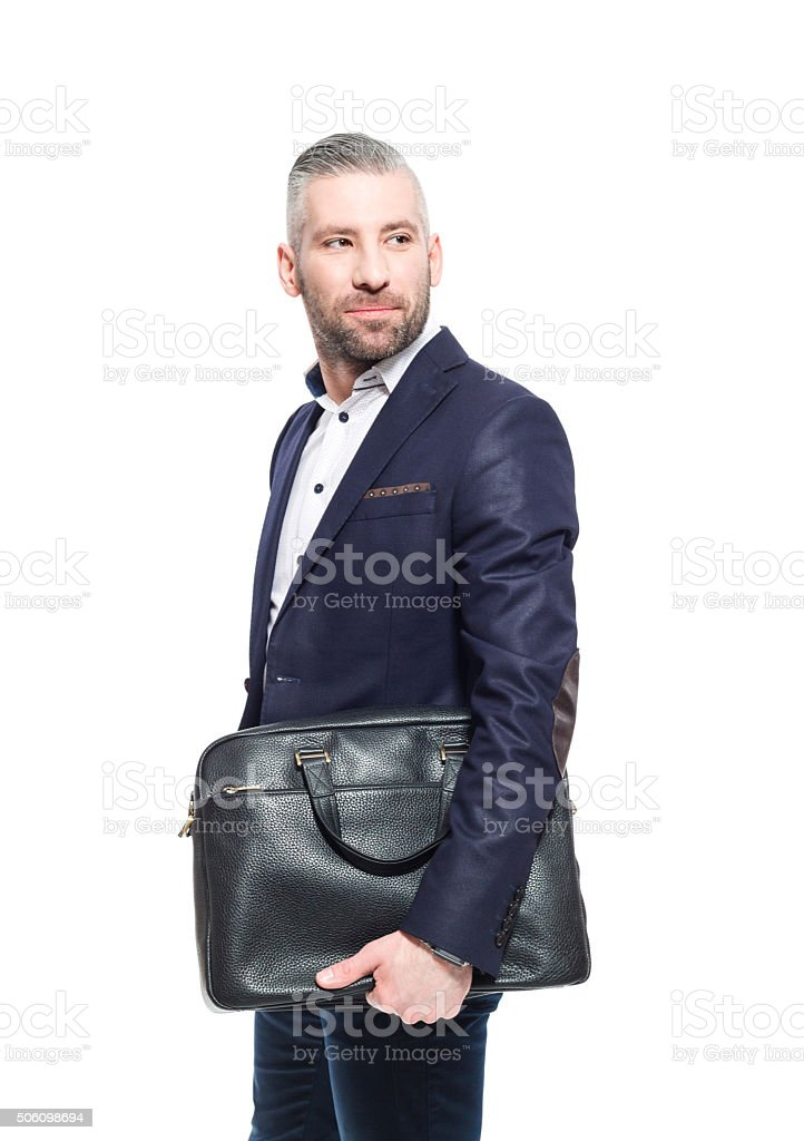 Handsome bearded grey hair businessman holding leather briefcase Portrait of elegant bearded grey hair businessman wearing suit standing against white background, holding briefcase. Studio shot, one person.  Adult Stock Photo
