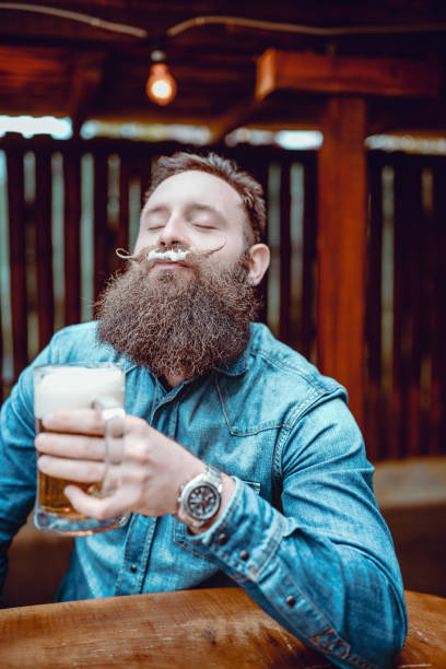Handsome Bearded Hipster Person Drinking Beer In Pub and Enjoying Handsome Bearded Hipster Person Drinking Beer In Pub and Enjoying facial hair stock pictures, royalty-free photos & images