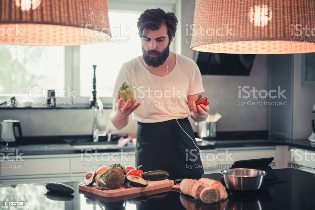 Handsome bearded man cooking and listening to music in the kitchen stock photo
