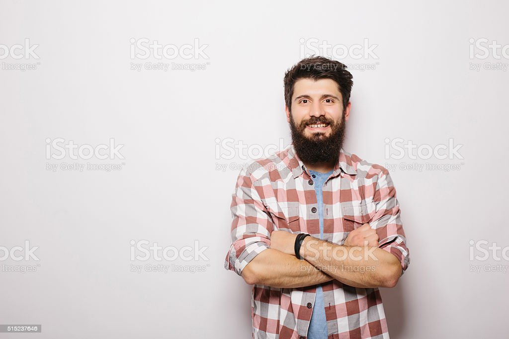 Handsome bearded man holding crossed hands  and looking at camera stock photo