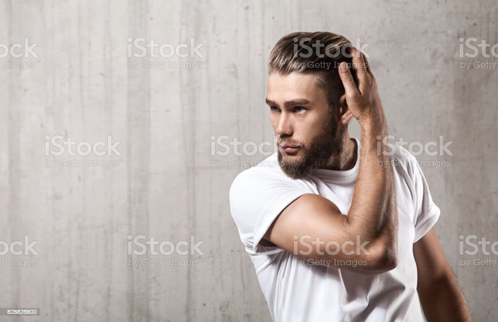 Handsome bearded man in a blank white t-shirt with stylish hair on a cement wall stock photo