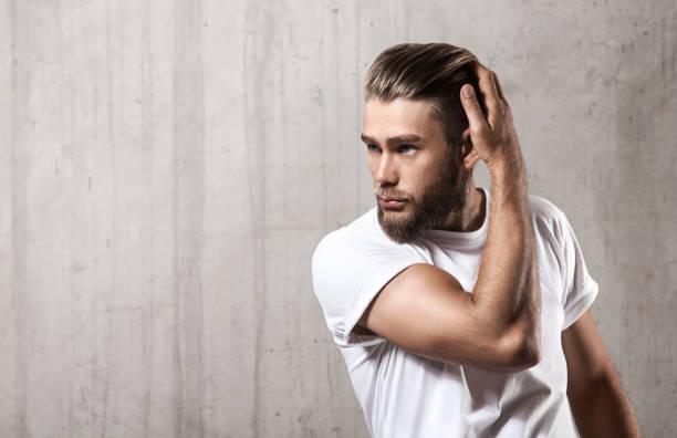 bärtiger mann ein leeres weißes t-shirt mit stilvollen haar auf einer betonmauer - männerfrisuren stock-fotos und bilder