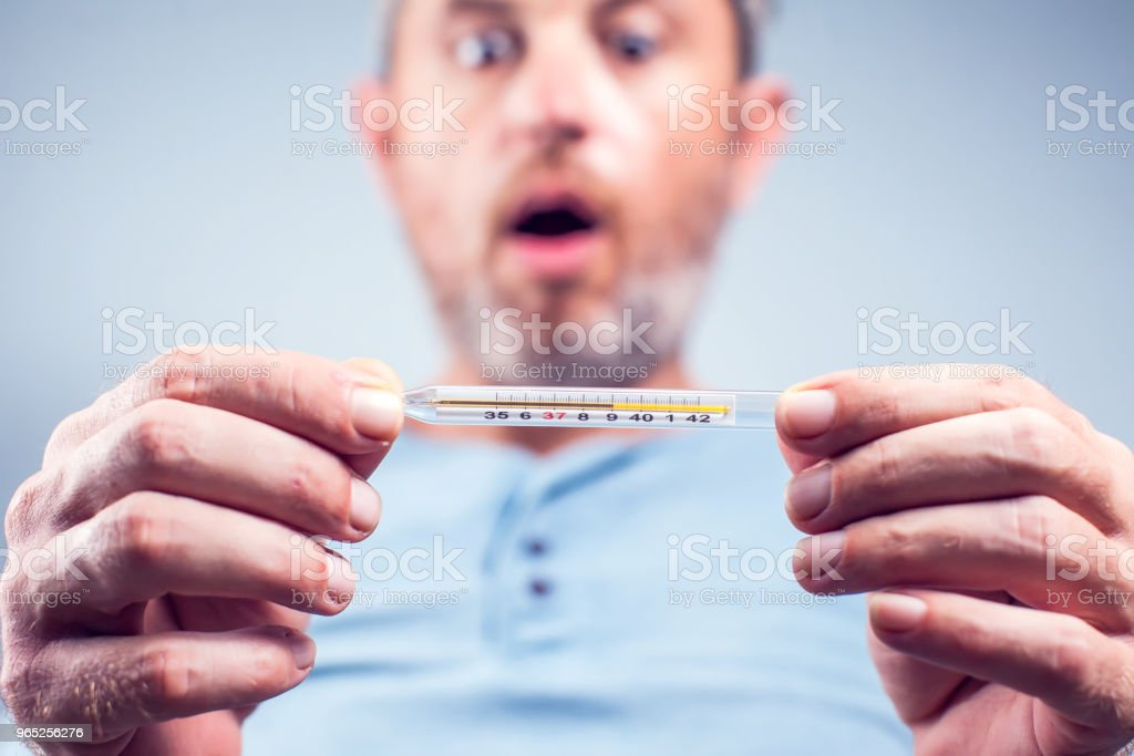 Handsome bearded man in a scarf holding thermometer isolated on a white background. Sad concerned guy is ill and looks at the thermometer, he has a temperature. Medicine concept zbiór zdjęć royalty-free
