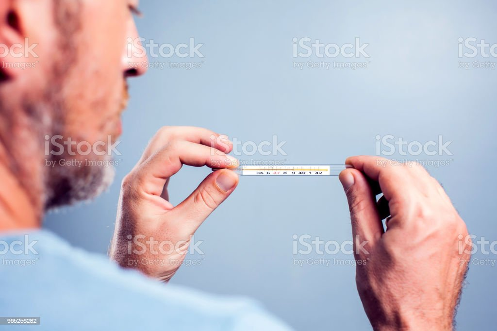 Handsome bearded man in a scarf holding thermometer isolated on a white background. Sad concerned guy is ill and looks at the thermometer, he has a temperature. Medicine concept royalty-free stock photo