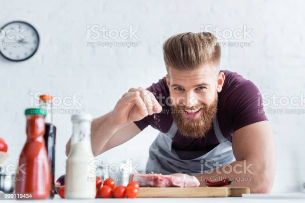 Handsome bearded man in apron cooking delicious steak and smiling at picture id999119434?b=1&k=6&m=999119434&s=612x612&h=zqpokspszjfpfim0sqk5fnqushxlmzx19k3kvddvhkq=