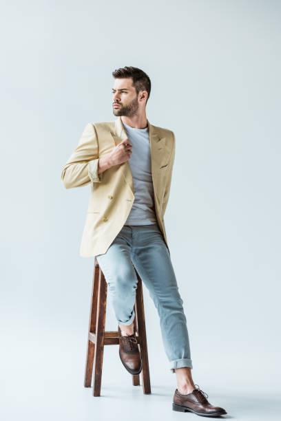 白い背景の上の椅子に座っているベージュのジャケットでハンサムなひげを生やした男 - ジャケット ストックフォトと画像
