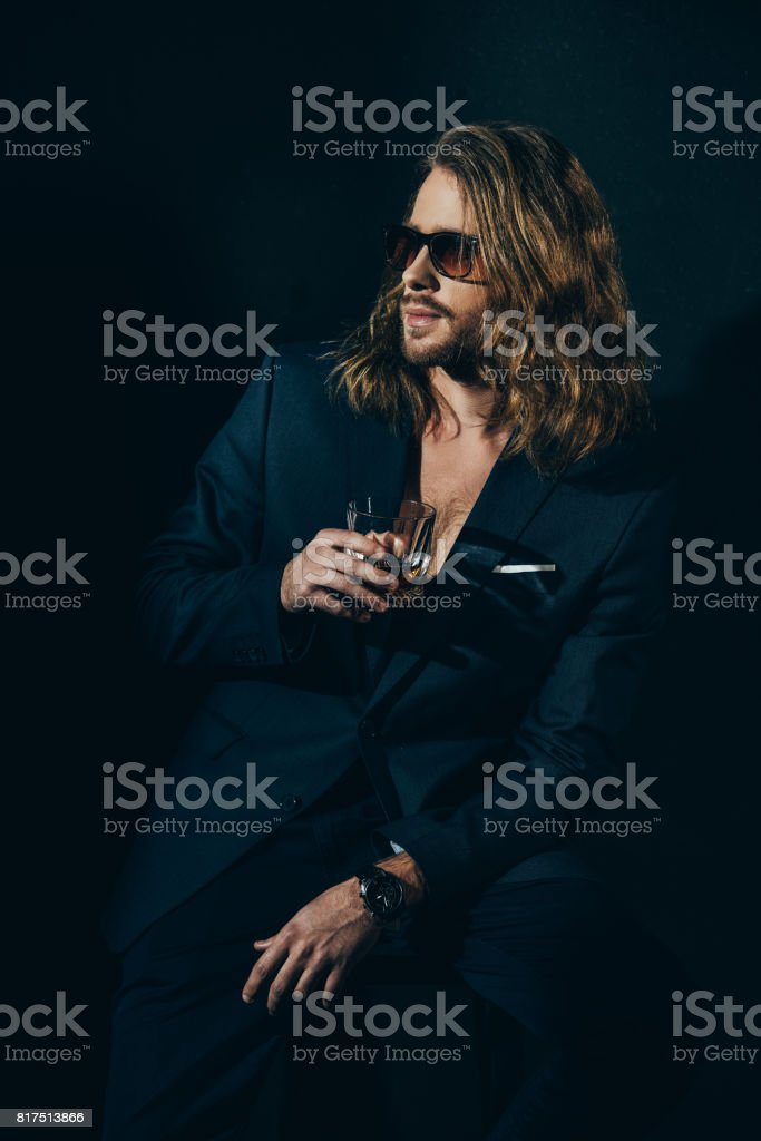 Handsome bearded man in fashionable suit holding glass of alcoholic beverage and looking away on black stock photo