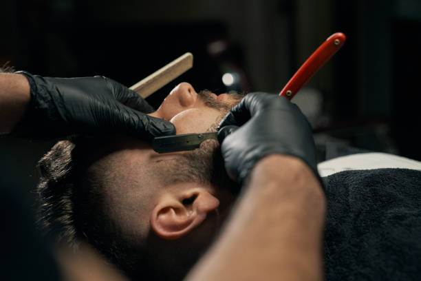Handsome bearded man is getting shaved by hairdresser stock photo