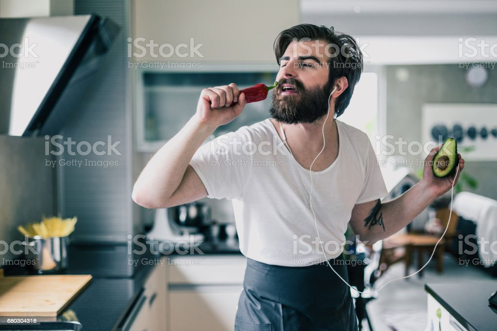 Handsome bearded man listening music, having fun and cooking healthy...