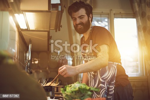 istock Handsome bearded man preparing food in the kitchen 688157282
