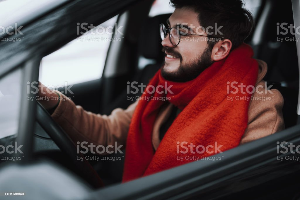 Driving with pleasure. Side view of man driving his auto while...