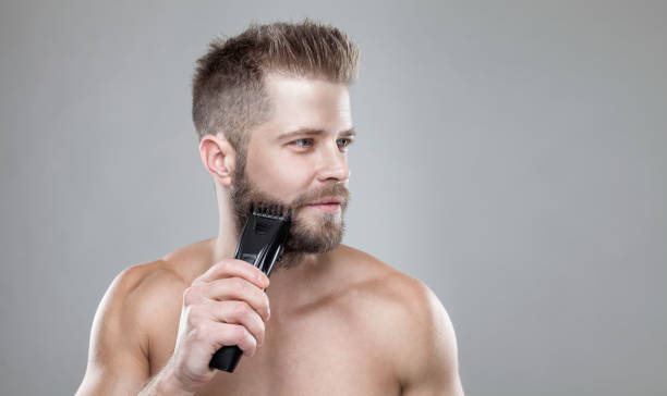 Handsome bearded man trimming his beard with a trimmer picture id858607264?b=1&k=6&m=858607264&s=612x612&w=0&h=bkvjya1hyrr hglayuim6wlqjndezmvuli1cwyrrgze=
