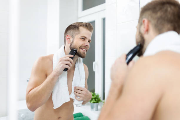 Handsome bearded man trimming his beard with a trimmer Handsome young bearded man trimming his beard with a trimmer facial hair stock pictures, royalty-free photos & images