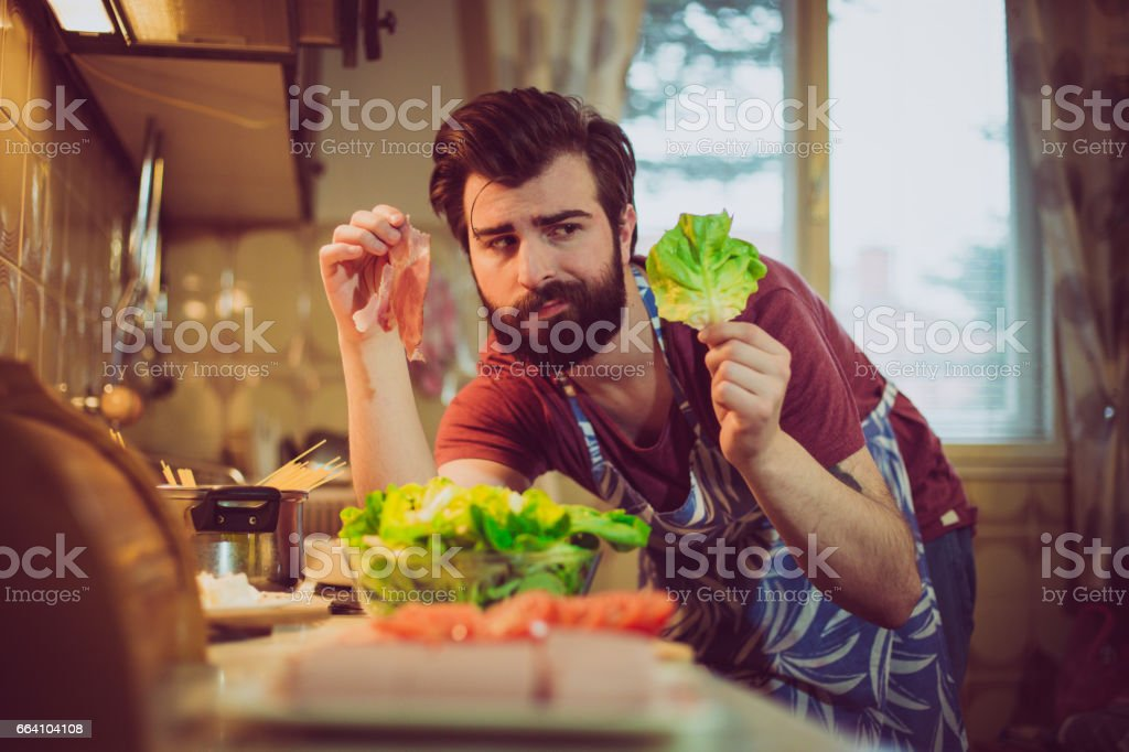 Handsome bearded man trying to decide between healthy and unhealthy meal foto stock royalty-free