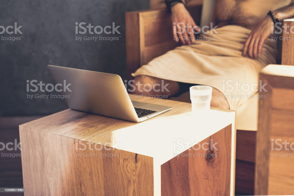 Handsome bearded Man using laptop computer while resting in spa...