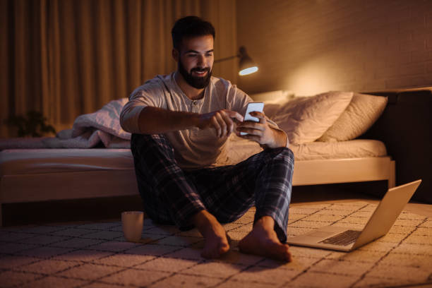 Handsome bearded man using phone in bedroom at night stock photo