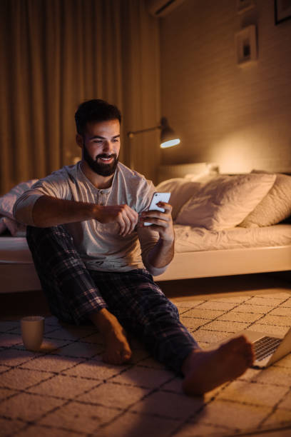 Handsome bearded man using smartphone in his bedroom at night stock photo