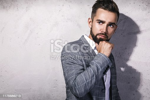 Handsome bearded man wearing gray suit is posing against concrete wall