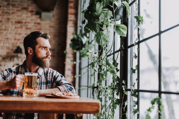 Handsome bearded man with drink spending time at pub stock photo