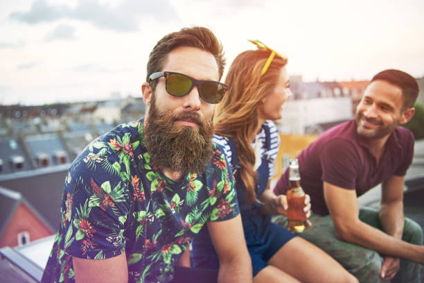 Handsome bearded man with friends on roof stock photo