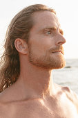 Handsome bearded man with shoulder length hair standing and at the beach staring into the summer sunshine with an intense serious expression and frown