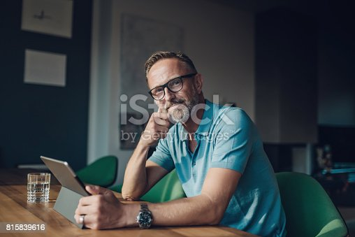 handsome smiling bearded midaged man at table with digital tablet