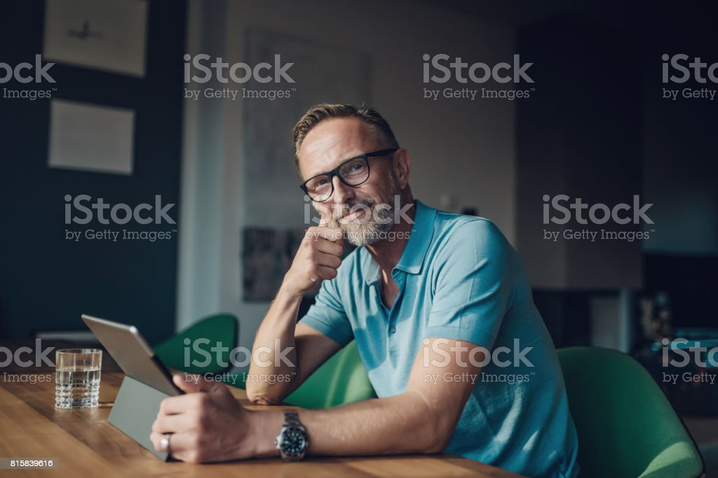 handsome bearded midaged man at table with digital tablet stock photo