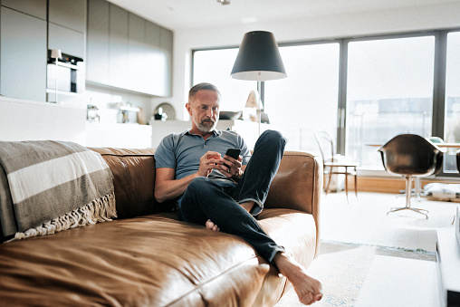 handsome  bearded mid aged man looking at mobile on sofa