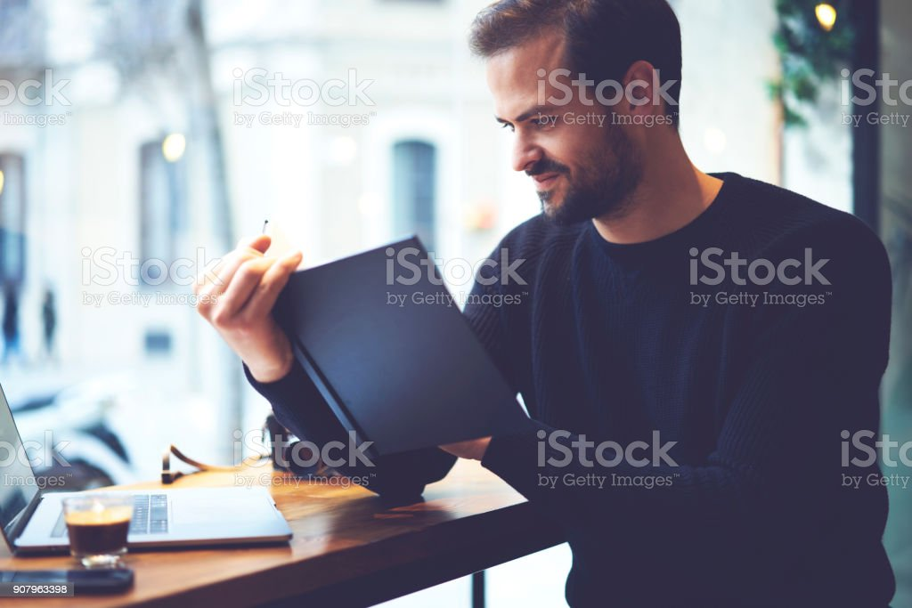 Handsome bearded owner of coffee shop sitting with laptop and checking financial documentation report written in notebook.Smiling male student reading interesting plot of new book during leisure time stock photo