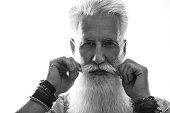 Stylish and handsome bearded senior man on white background