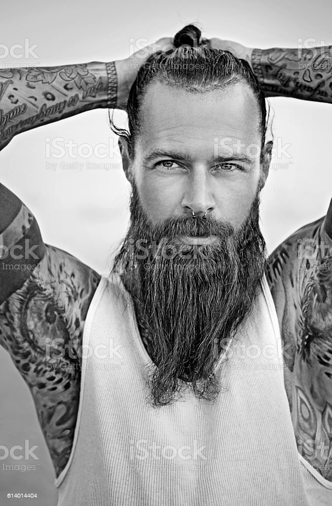 Handsome bearded tattooed man posing for portrait stock photo