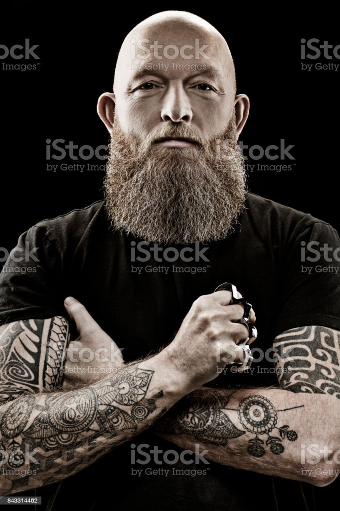 Handsome bearded tattooed middle aged man in studio shoot stock photo