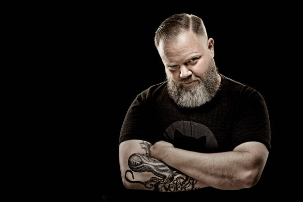 Handsome bearded tattooed middle aged man in studio shoot Handsome bearded tattooed middle aged man in studio shoot macho stock pictures, royalty-free photos & images