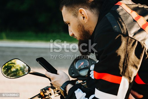istock Handsome bearded traveler leaning on his bike while looking into smartphone to find the route near the road. 970489842