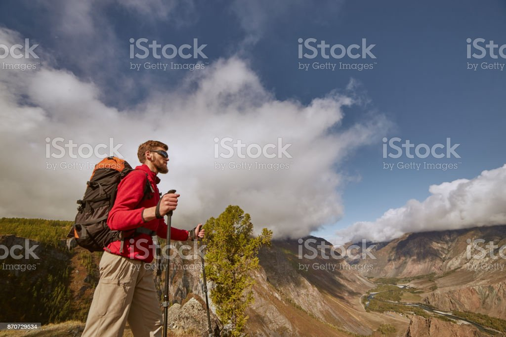 Handsome bearded young male hiker sitting on the edge of a canyon looking away stock photo