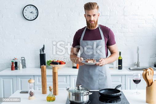 istock handsome bearded young man in apron holding delicious beef steak on plate and looking at camera 999093884