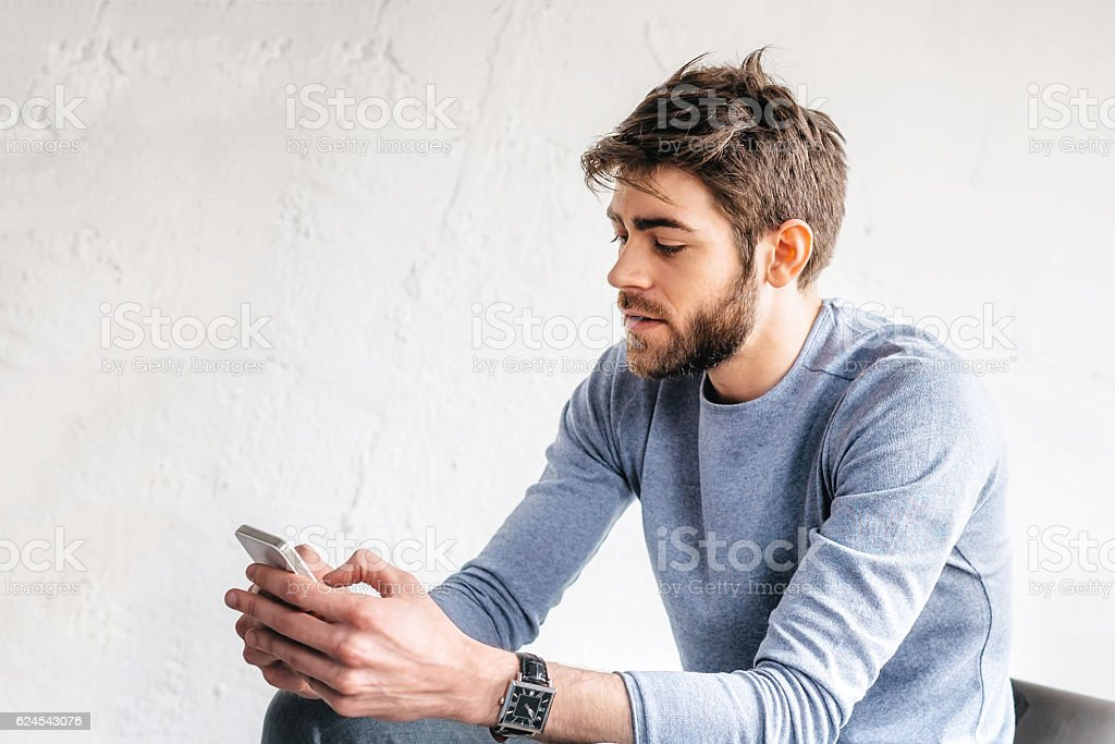 handsome happy bearded young man with mobile in Paris loft