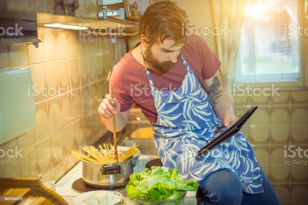 Handsome bearded young man making healthy meal stock photo