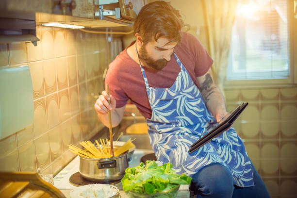 Handsome bearded young man making healthy meal Handsome bearded young man making healthy meal spaghetti straps stock pictures, royalty-free photos & images
