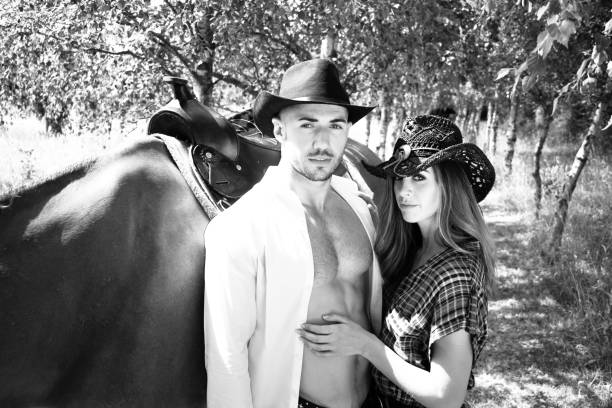 Handsome, beautiful Cowboy and cowgirl couple with horse and saddle on ranch holding and kissing on ranch stock photo
