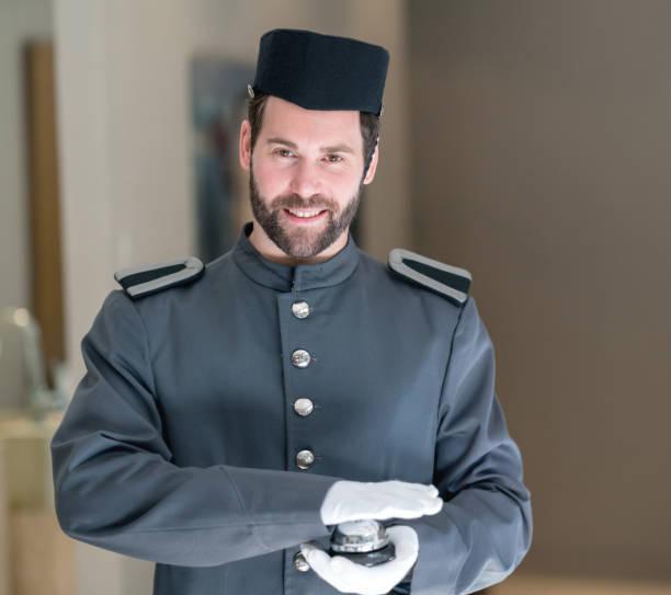 Hermoso bellman en el hotel mirando a la cámara sonriendo - foto de stock