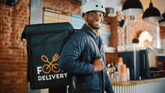 Handsome Black African American Food Delivery Courier Posing in Front of the Camera in a Coffee Shop. Happy and Smiling Man Wearing a Bicycle Helmet and Thermal Insulated Bag for Food on His Back.