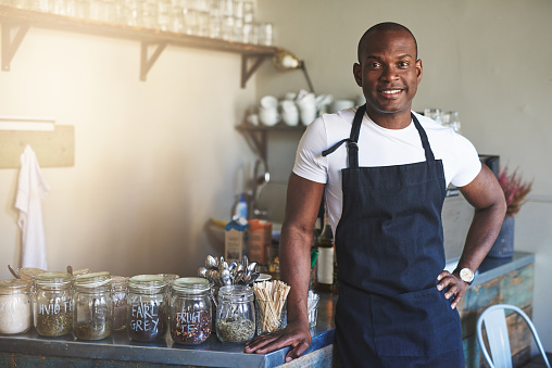 istock Handsome black entrepreneur stands by cafe counter 683527302