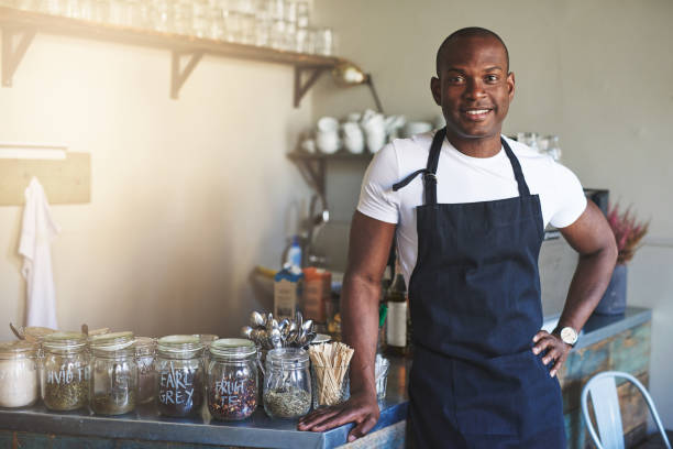 Handsome black entrepreneur stands by cafe counter stock photo