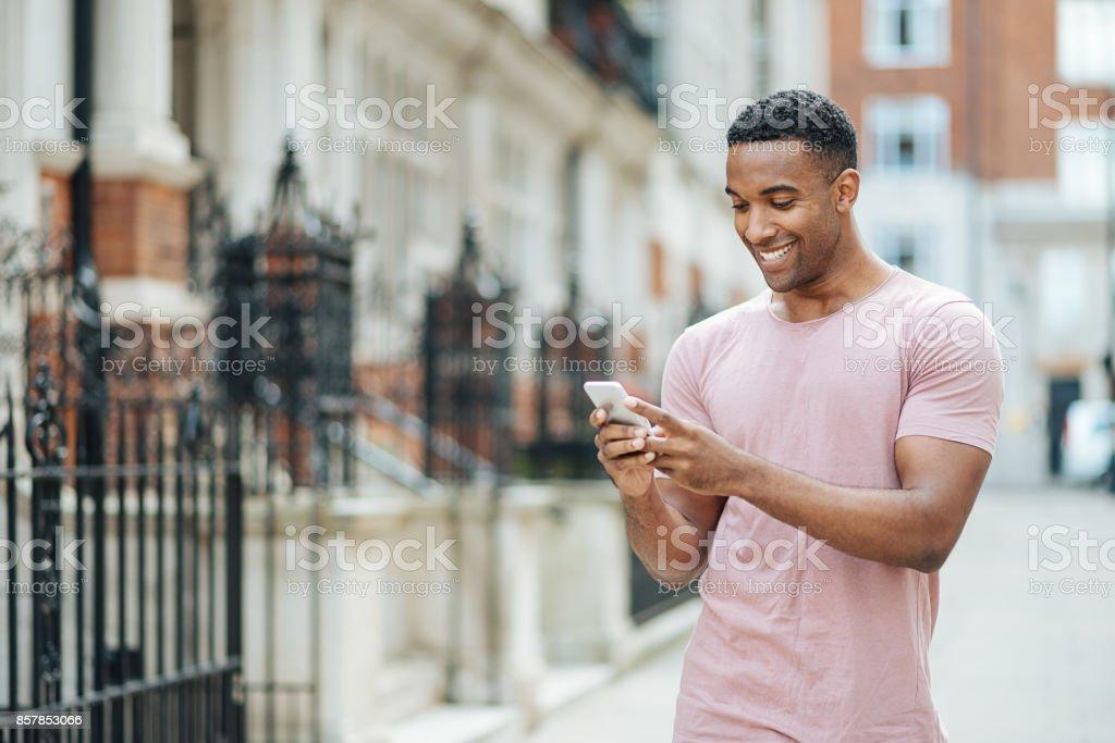 Handsome black guy in London, using mobile phone stock photo