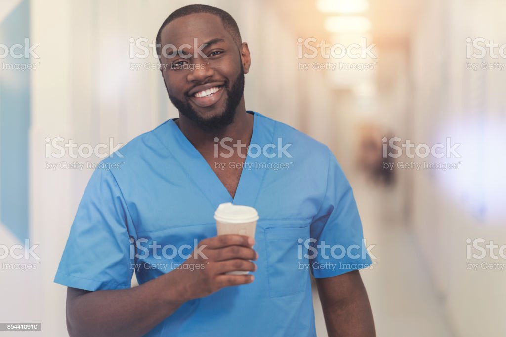 Handsome black man holding paper cup with coffee stock photo